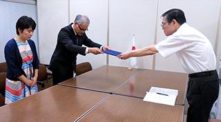 内閣府に対し申し入れを行う幸福実現党の佐々木勝浩、外交部会の服部まさみ。