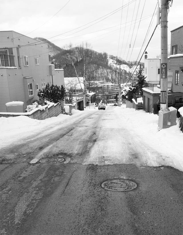 現場の坂道の様子。凍りやすく、自動車のスリップが起こりやすい。「坂の上側(写真手前)はロードヒーティングが設置されているが、溶けた水が坂の途中でこぼこに凍って危険。側溝を設置できないか」との要望が寄せられた。