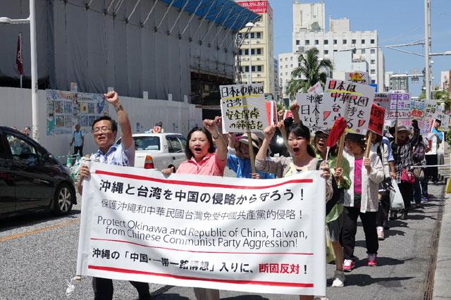 デモ隊の先頭に立つ党幹事長の松島ひろのり(写真左)、党沖縄県本部の下地玲子代表(同中央)。