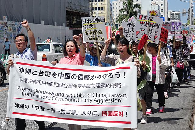 デモ隊の先頭に立つ松島ひろのり党幹事長(写真左)、党沖縄県本部の下地玲子代表(同中央)。