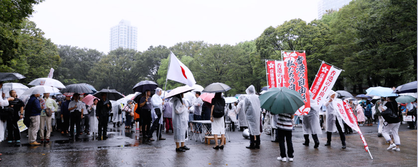 雨の中、出発地点の公園に続々と参集するデモ参加者