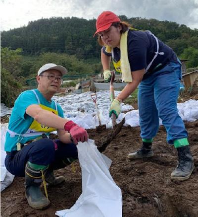残土を土嚢袋に詰める作業をするいき愛子神奈川県統括支部代表(右)